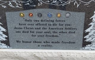 """Large stone memorial installed on a government-run property at Monument Cemetary, CO bearing all military branch insignia with the inscription """"Only two defining forces have ever offered to die for you, Jesus Christ and the American soldier. One died for your soul, the other died for your freedom. We honor those who made freedom a reality."""""""