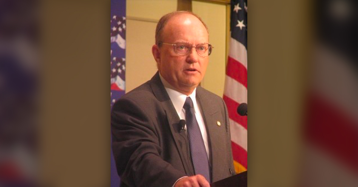 Colonel Lawrence Wilkerson at a lectern with American flags behind.