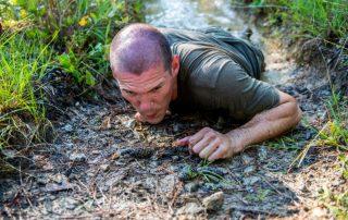 Army Ranger student crawling through mud