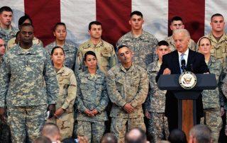 President Biden at podium speaking to soldiers