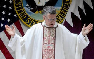 Arch Bishop of Military Services Timothy Broglio in Arch Bishop robes with hands raised in prayer